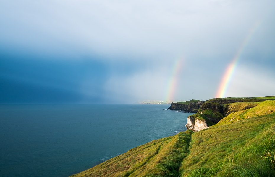 dunluce and dunsaverick castles in northern ireland with rainbow